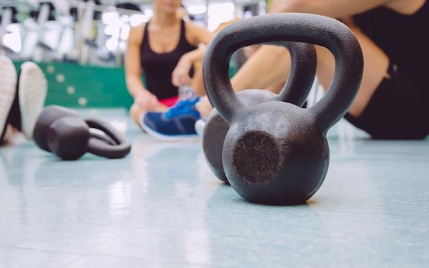 Zbliżenie czarny żelazny kettlebell i grupa ludzi siedzących na podłodze w centrum fitness w tle