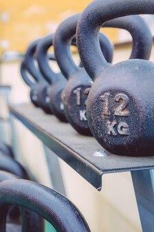 Zbliżenie czarnych żelaznych rzędów kettlebells z różnymi ciężarami gotowymi do użycia w centrum fitness