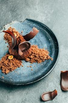 Zbliżenie: czekoladowe ciasteczko w czarnej tablicy na szarym betonie