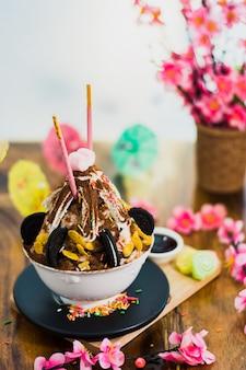 Zbliżenie czekoladowy bingsu na tacy, bingsu lub bingsoo, koreańczyk golił lodowego deser z słodkimi polewami a