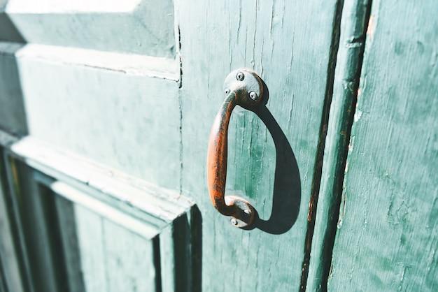 Zbliżenie czerwona farby rękojeść na starym zielonym drzwi.
