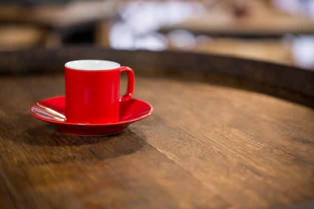 Zbliżenie: czerwona filiżanka i spodek na stole w kawiarni
