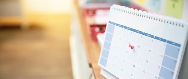 Zbliżenie czerwoną szpilkę na pustym kalendarzu biurkowym.