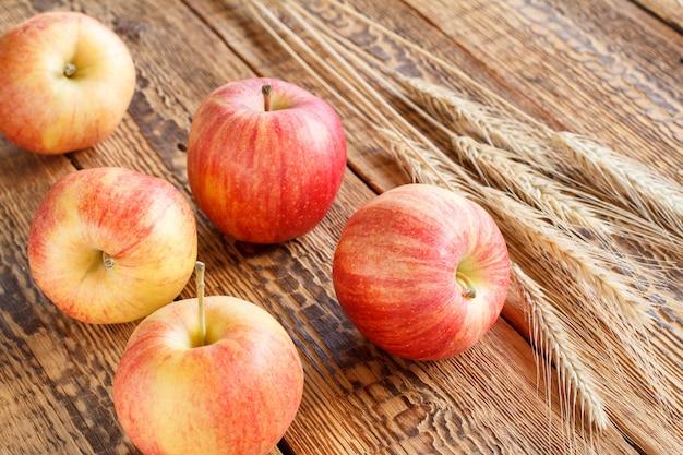 Zbliżenie czerwone jabłka i pszenica uszy na drewnianym tle. mała głębia ostrości.