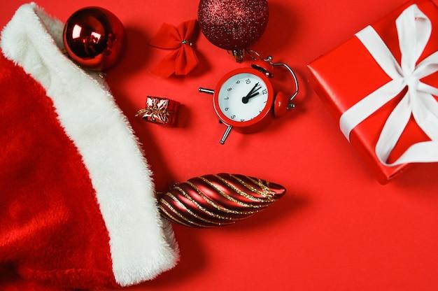 Zbliżenie czerwone ozdoby świąteczne pudełko i budzik na czerwonym tle