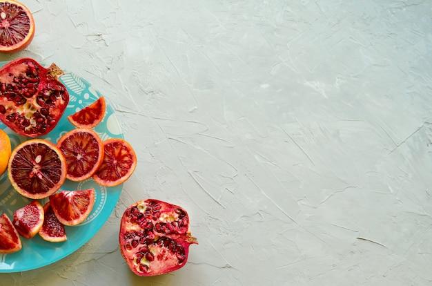 Zbliżenie czerwonej sycylijskiej krwi (krwawe) pomarańcze - pokrojone i pokrojone, dojrzałe i smaczne z miejsca kopiowania, szary cementowy tło