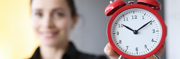 Zbliżenie czerwony budzik w rękach koncepcji harmonogramu pracy młodej kobiety