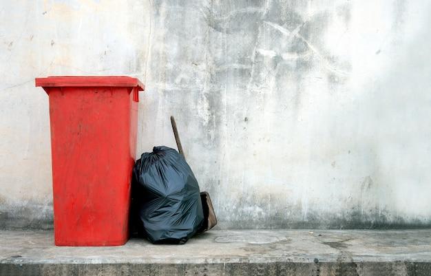 Zbliżenie czerwony kosz na śmieci z soft-focus i overlight w tle