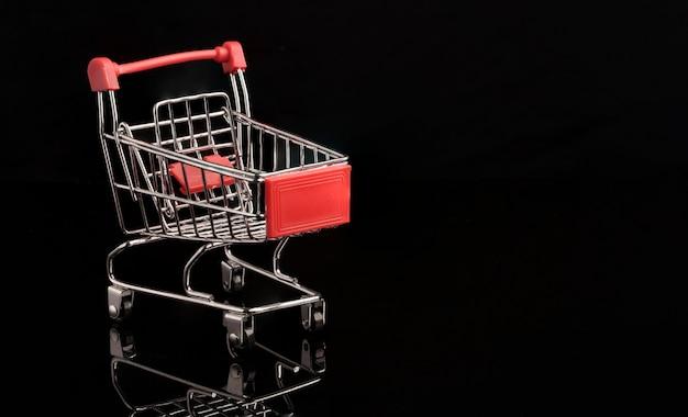 Zbliżenie czerwony wózek na zakupy wózek z odbiciem na czarnym tle, handel i koncepcja zakupy.
