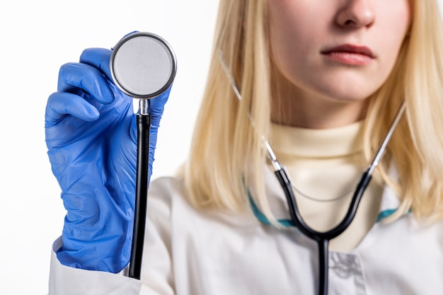 Zbliżenie części stetoskopu, którą lekarz przykłada do klatki piersiowej pacjenta