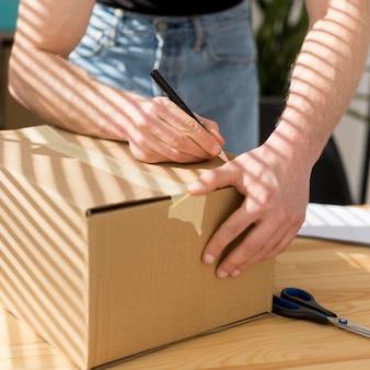 Zbliżenie: człowiek pakuje pudełko