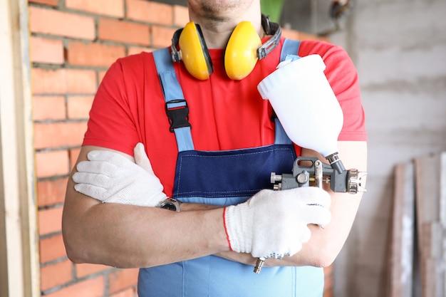Zbliżenie: człowiek pracownika stojącego ze skrzyżowanymi rękami na ścianie z czerwonej cegły. profesjonalny majster w mundurze i białych rękawiczkach. zszywacz w dłoni. nowy projekt domu i koncepcja remontu
