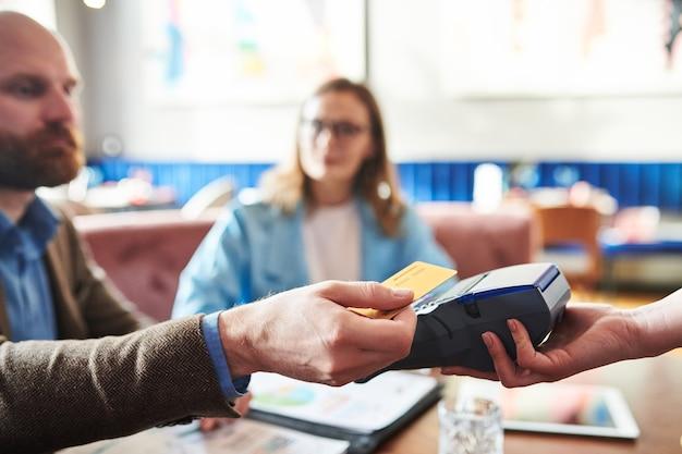 Zbliżenie: człowiek umieszczenie karty kredytowej w terminalu płatniczym podczas korzystania z płatności bezgotówkowej w kawiarni