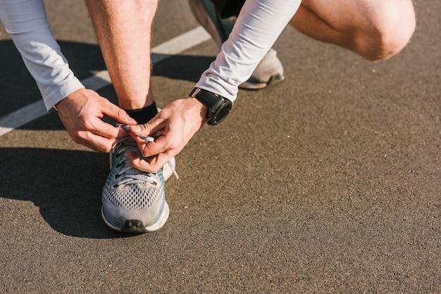 Zbliżenie: człowiek wiązanie sznurówki do butów