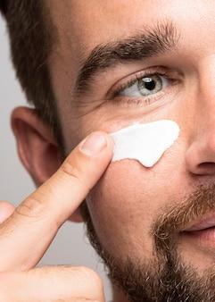 Zbliżenie: człowiek za pomocą kremu do twarzy