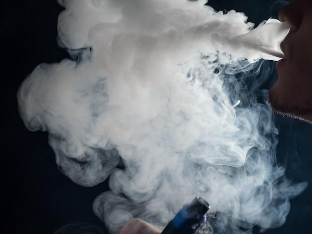 Zbliżenie człowieka-mężczyzny wydycha chmurę pary. mod elektroniczny papieros