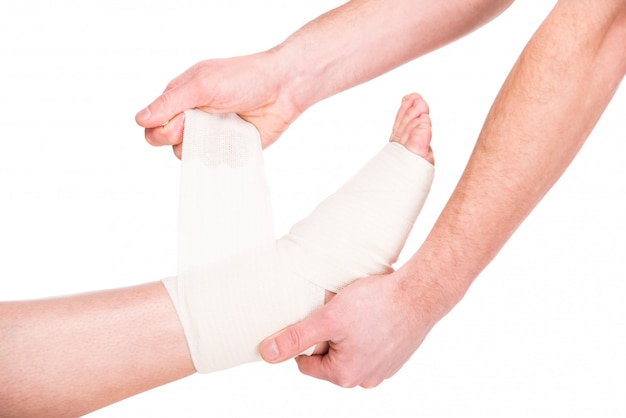 Zbliżenie człowieka nakłada bandaż na zranione stopy.