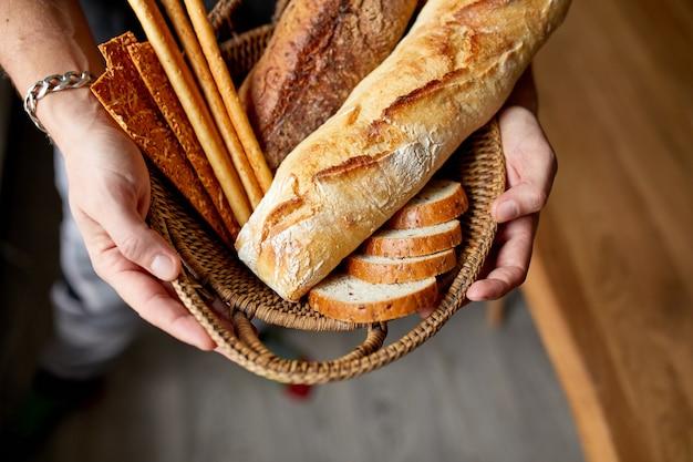 Zbliżenie człowieka posiadającego kosz z różnych chlebów świeżo upieczonych