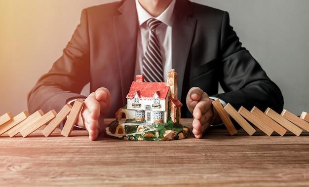Zbliżenie człowieka powstrzymującego upadek drewnianych klocków na model domu. koncepcja ubezpieczenia i bezpieczeństwa domu.