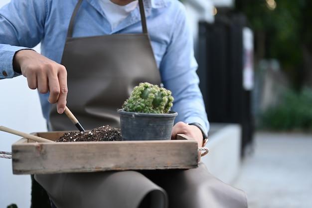 Zbliżenie człowieka rąk sadzenia kaktusa do garnka w swoim przydomowym ogrodzie kielnią.