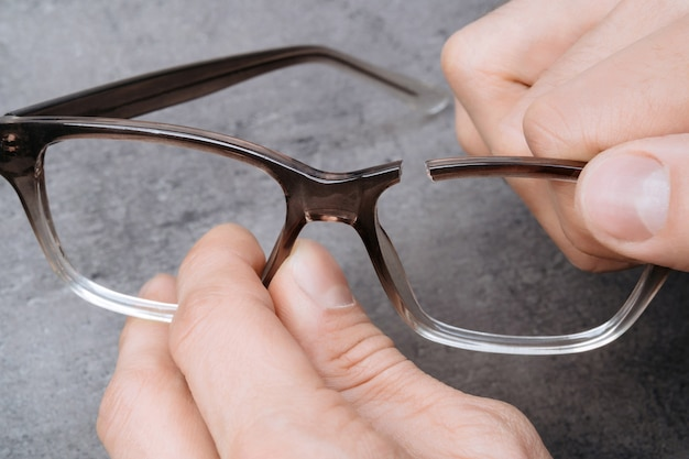 Zbliżenie człowieka ręce trzymając złamaną ramkę okularów. młody optometrysta trzymający w dłoniach sprawdził żebra okularów.