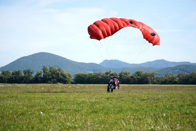Zbliżenie człowieka skaczącego na spadochronie w pobliżu ziemi z czerwonym spadochronem w ciągu dnia