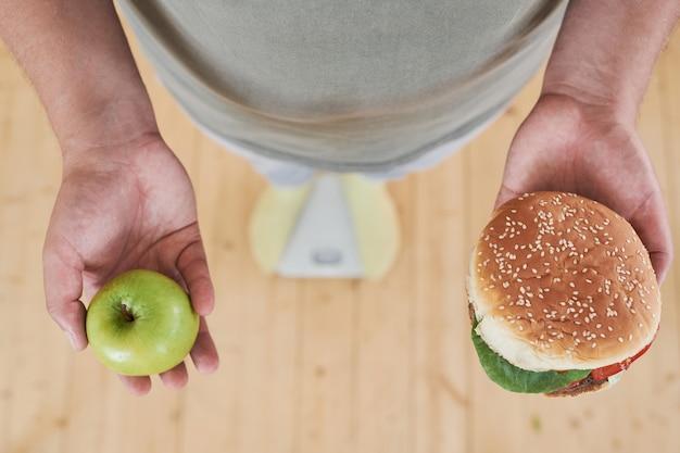 Zbliżenie człowieka stojącego na wadze i trzymającego jabłko w jednej ręce i hamburgera w drugiej, aby zrobić d...