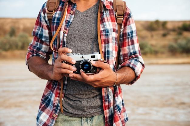 Zbliżenie człowieka w kraciastej koszuli stojącej i trzymającej stary vintage zdjęcie przód