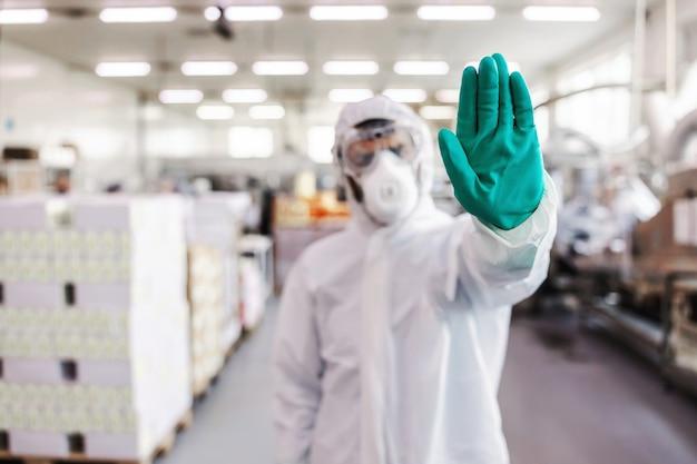 Zbliżenie człowieka w mundurze ochronnym z gumowymi rękawiczkami stojąc w fabryce żywności i pokazując znak stop ręką. koncepcja epidemii wirusa koronowego.