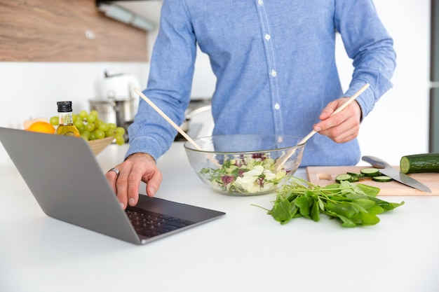 Zbliżenie człowieka w niebieskiej koszuli za pomocą laptopa i robienie sałatki w szklanej misce w kuchni