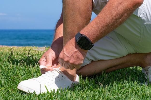 Zbliżenie człowieka wiązania sznurowadeł do butów. mężczyzna fitness biegacz przygotowuje się do biegania na świeżym powietrzu wiosną lub latem.
