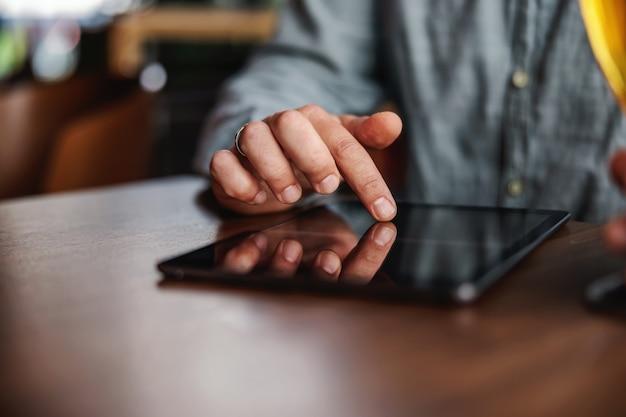 Zbliżenie człowieka za pomocą tabletu do zawieszania na mediach społecznościowych, siedząc w barze.