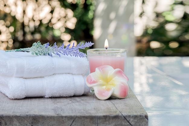 Zbliżenie czyści ręczniki z różową świeczką i kwiatem na drewnianym stole