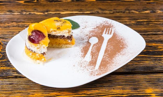 Zbliżenie dekadenckiego ciasta owocowego pokrojonego na pół i podanego na białym talerzu z posypanym kakao na powierzchni drewnianego stołu