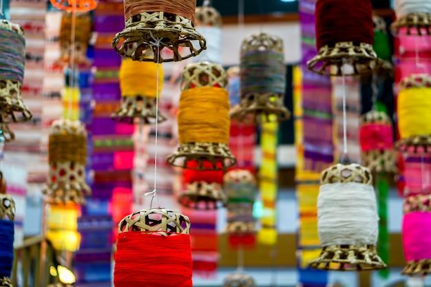 Zbliżenie dekoracyjny łozinowy lampion i lanna tkaniny długie flaga wieszają na hotelowym lobby suficie i rozmytym tle.