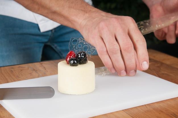 Zbliżenie dekoruje lody z lodem przy stołem mężczyzna