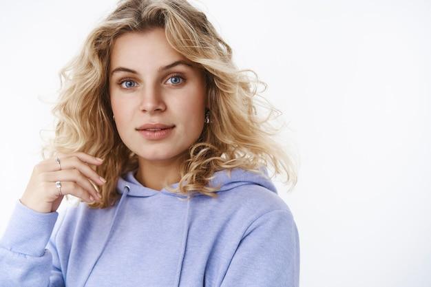 Zbliżenie delikatna i kobieca młoda blond kobieta z lat 20. o niebieskich oczach w ciepłej bluzie z kapturem patrząca szczerze i zainteresowana w aparacie lekko otwarte usta bawiące się lokami, myśląc nad białą ścianą