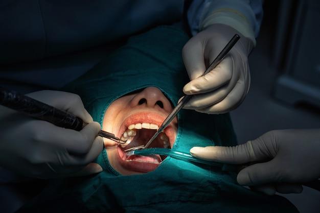 Zbliżenie dentysta i asystent operacyjny do sprawdzania i czyszczenia zębów w klinice dentystycznej