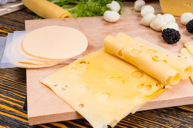 Zbliżenie deski serów z pokrojonym serem szwajcarskim i provolone oraz przyozdobionym owocami, podawane na rustykalnym drewnianym stole z słojami drewna