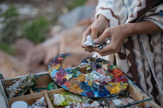 Zbliżenie dłoni artysty malowanie obrazu na płótnie, szukając inspiracji na zewnątrz