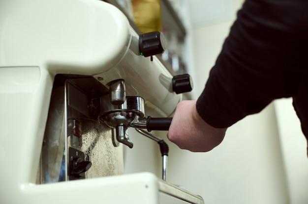 Zbliżenie dłoni baristy trzymającej kolbę z mieloną kawą na tle profesjonalnego ekspresu do kawy