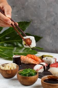 Zbliżenie dłoni biorąc rolki pałeczkami z płyty w barze sushi