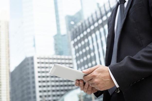 Zbliżenie dłoni biznesmen pracujący przy użyciu cyfrowego tabletu pc, stojąc z przodu