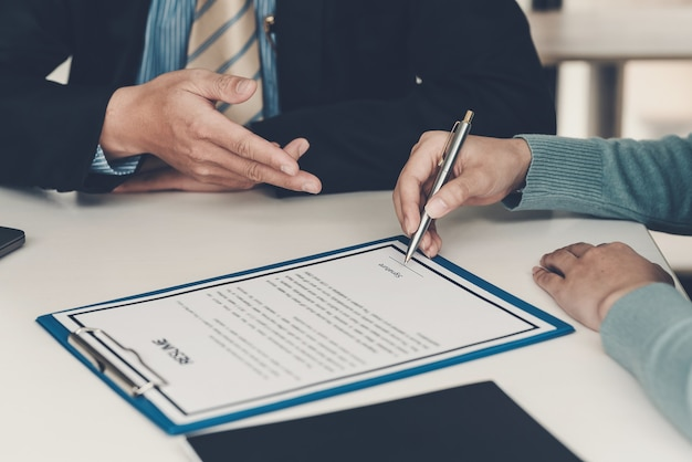 Zbliżenie dłoni biznesmen wskazując na dokument do klienta trzymającego pióro do podpisywania dokumentów umowy w biurze.