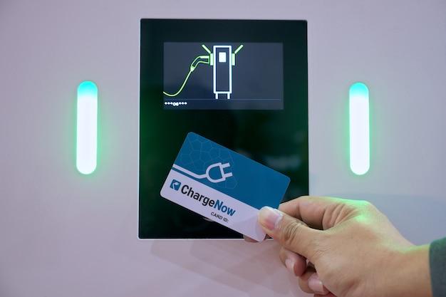 Zbliżenie dłoni biznesmena, który za pomocą karty inteligentnej dotyka czujnika monitora do akumulatora