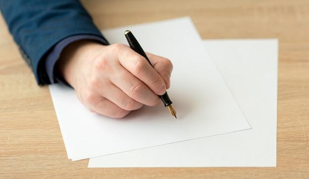 Zbliżenie dłoni biznesmena w garniturze, piszącego list lub podpisującego dokument na kartce białego papieru wiecznym piórem ze stalówką