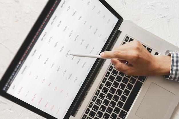 Zbliżenie dłoni biznesmena z patelni, patrząc na szczegóły giełdy na laptopie