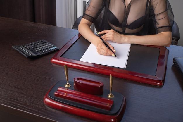 Zbliżenie dłoni bizneswoman podpisywania dokumentów na biurku