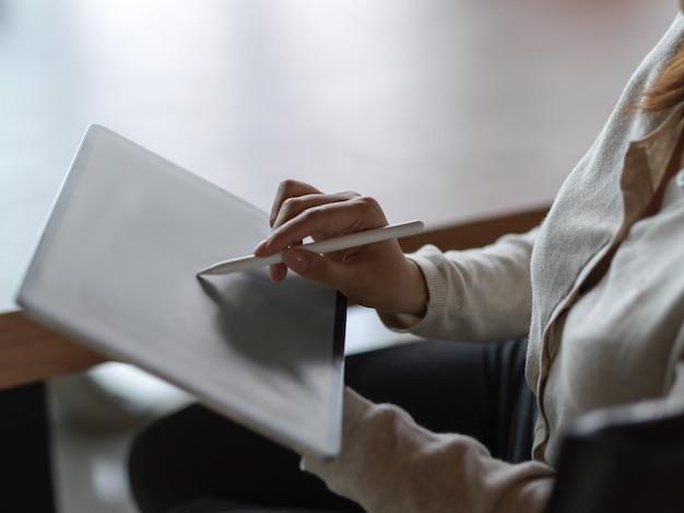 Zbliżenie dłoni bizneswoman pracy na cyfrowym tablecie z rysikiem i rozmytym tłem