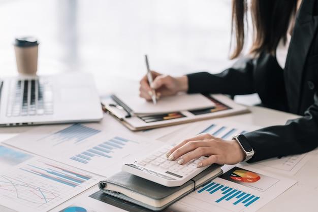 Zbliżenie dłoni bizneswoman robi obliczenia za pomocą dokumentu kalkulatora umieszczonego na stole biurowym.